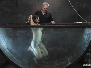 Nadia Styles is all tied up except for one leg. She's in a large tank and is told when to go under and to come back up. Then she gets pushed under, getting nervous all the while. Although this is all strange, it's still worth watching to see those huge tits of hers all wet!