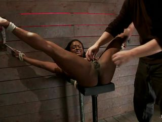 She's a slutty black lady and loves to be tied up hard and fucked. Here she is with her sexy legs spread wide and her shaved cunt stimulated by a black dildo. She moans with pleasure as the women applies that sex toy on her pussy and how knows, maybe she's a bout to stick something big and hard in that hot vagina.