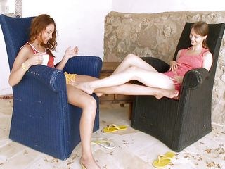 Beata and Vika are getting along just fine. These bitches with hot legs, small tits are hot and horny and Beata uses her feet to rub Vika's pussy making her very aroused. Now the chicks are turned on and we can enjoy watching them having some lesbian love with nipples sucking, tits licking and perhaps a lot more.